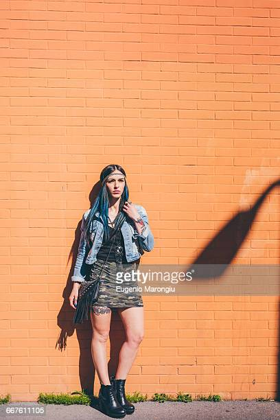 Portrait of young woman with dip dyed blue hair leaning against orange wall