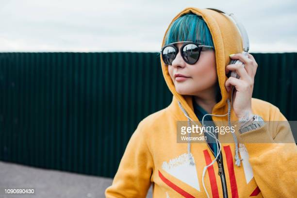 portrait of young woman with dyed blue hair listening music with headphones - excéntrico fotografías e imágenes de stock
