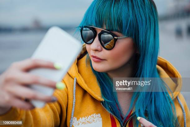 portrait of young woman with dyed blue hair taking selfie with smartphone - dyed hair stock pictures, royalty-free photos & images