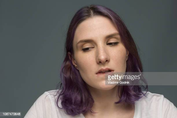 portrait of young woman with dyed hair and biting lip - biting lip stock pictures, royalty-free photos & images