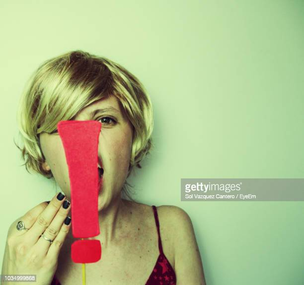 Portrait Of Young Woman With Exclamation Point Against White Background