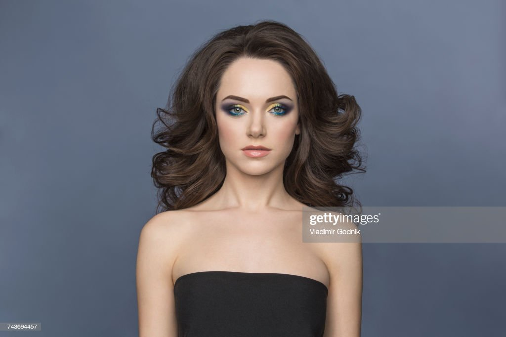 Portrait of young woman with eye make-up wearing strapless top against gray background : Stock Photo