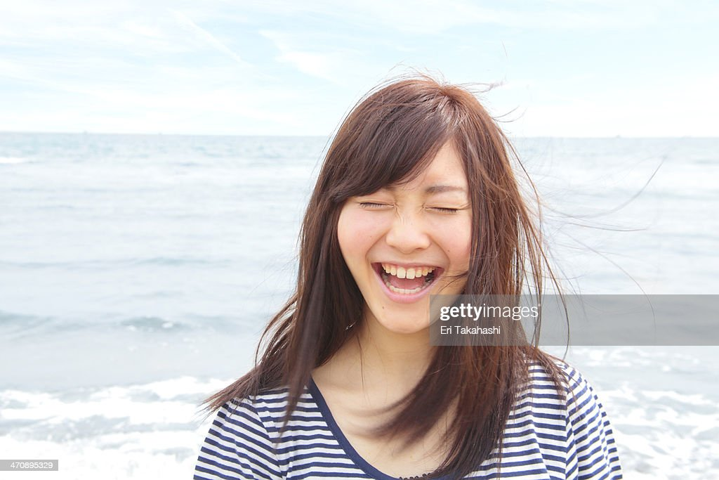 Portrait of young woman with eyes closed, laughing : Stock Photo