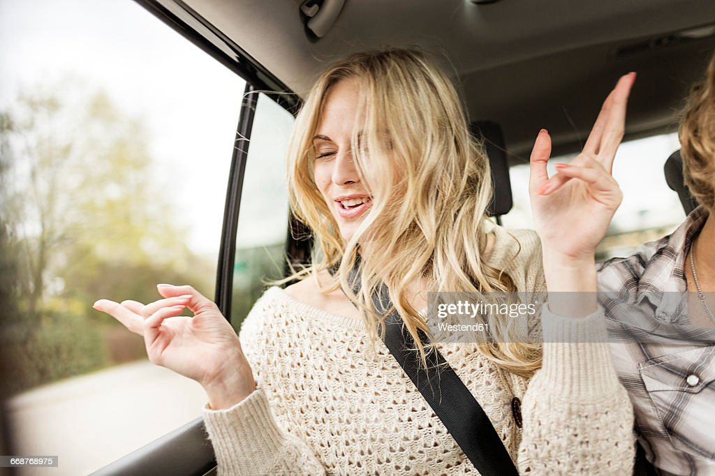 Portrait of young woman with eyes closed listening music in a car : Stock-Foto