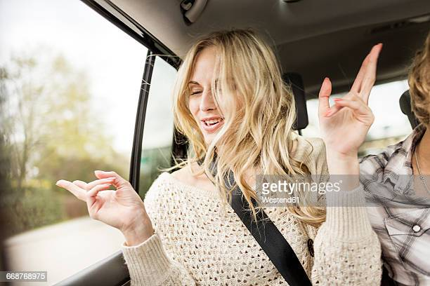 portrait of young woman with eyes closed listening music in a car - cantare foto e immagini stock