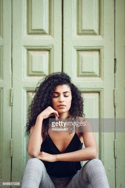 portrait of young woman with eyes closed sitting in front of an entrance door - schwarzes haar stock-fotos und bilder