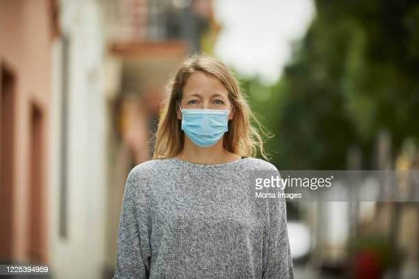 portrait of young woman with face mask on the street - pollution mask stock pictures, royalty-free photos & images