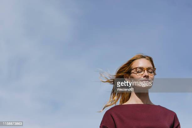 portrait of young woman with glasses and closed eyes under blue sky - einfaches leben stock-fotos und bilder