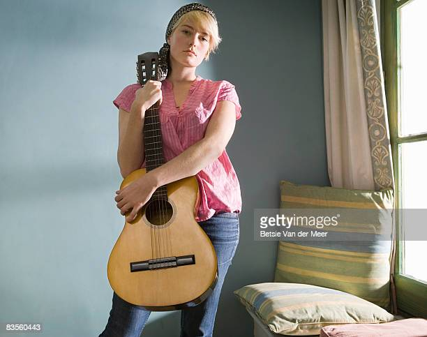 Portrait of young woman with guitar.