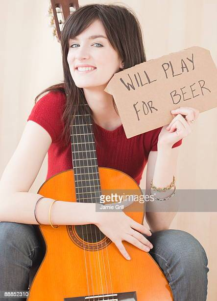 Portrait of young woman with guitar, playing for beer