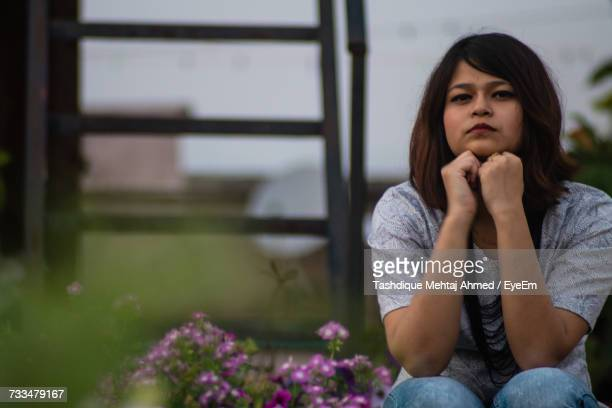 Portrait Of Young Woman With Hand On Chin Sitting Against Plants