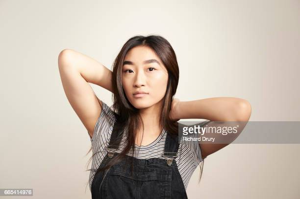 portrait of young woman with hands behind head - bib overalls stock pictures, royalty-free photos & images