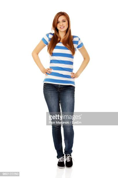 portrait of young woman with hands on hip against white background - spijkerbroek stockfoto's en -beelden