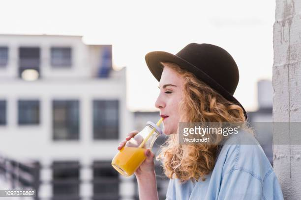 portrait of young woman with hat drinking beverage - juice drink stock pictures, royalty-free photos & images