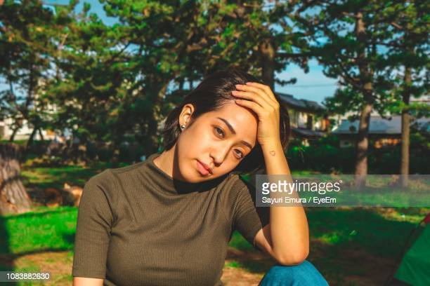 Portrait Of Young Woman With Head In Hand Sitting At Park