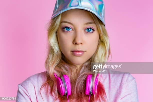 Portrait of young woman with headphones and basecap in front of pink background