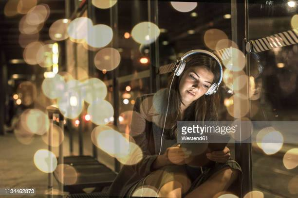 portrait of young woman with headphones and tablet waiting at station by night - ljus naturföreteelse bildbanksfoton och bilder