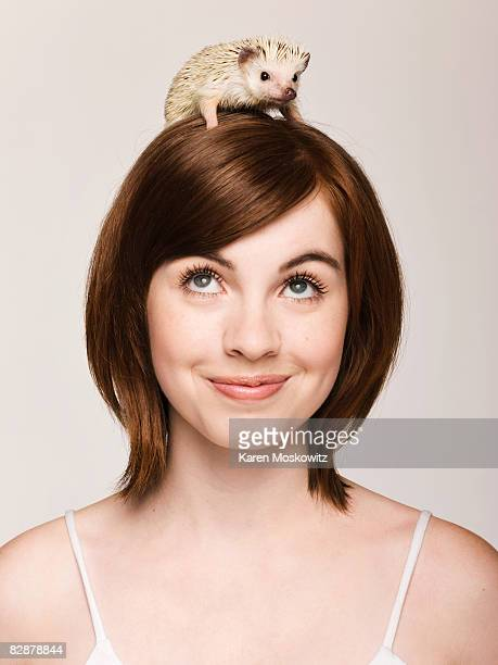 portrait of young woman with hedgehog on her head