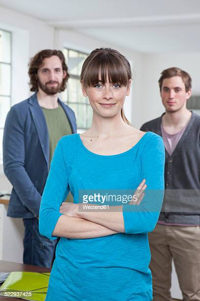 Portrait of young woman with her two colleagues in the background standing in a creative office