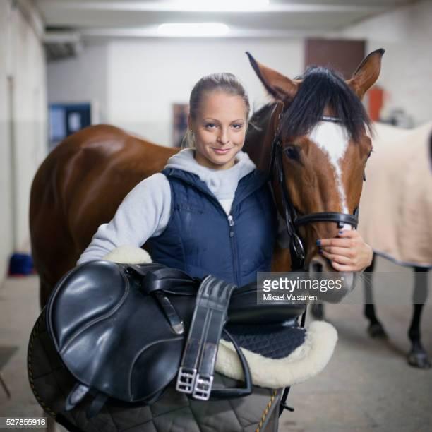 portrait of young woman with horse in stables - andare a cavallo foto e immagini stock