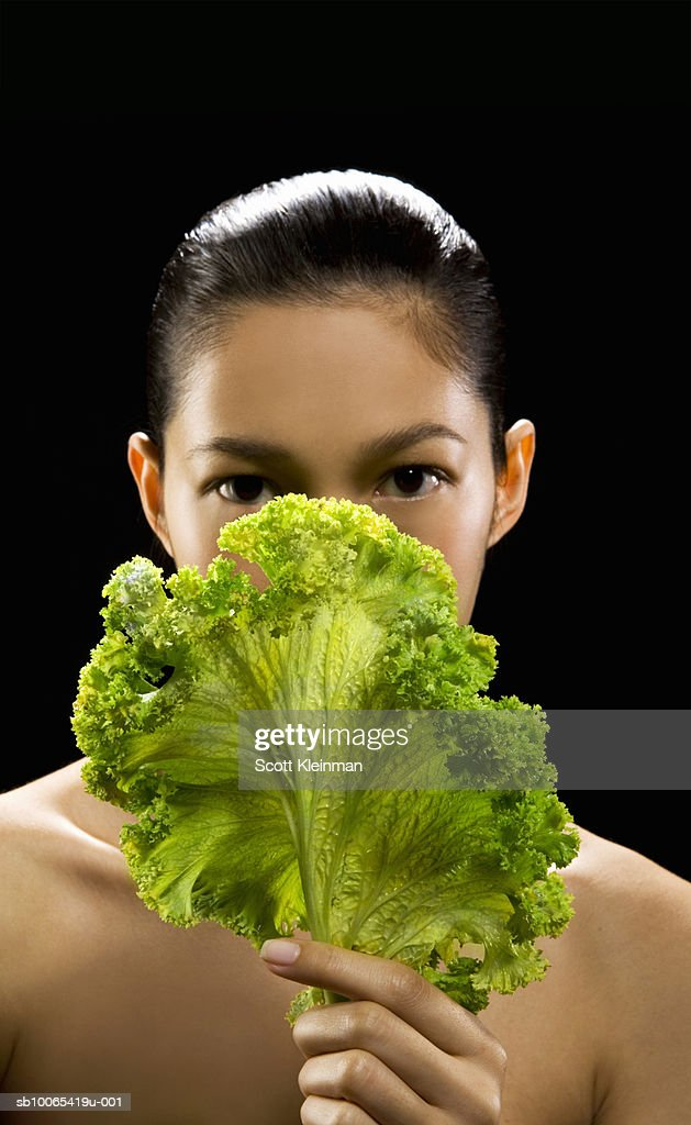 Portrait of young woman with kale leaf, black background : Foto stock