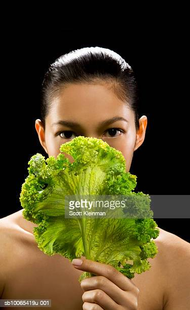 Portrait of young woman with kale leaf, black background