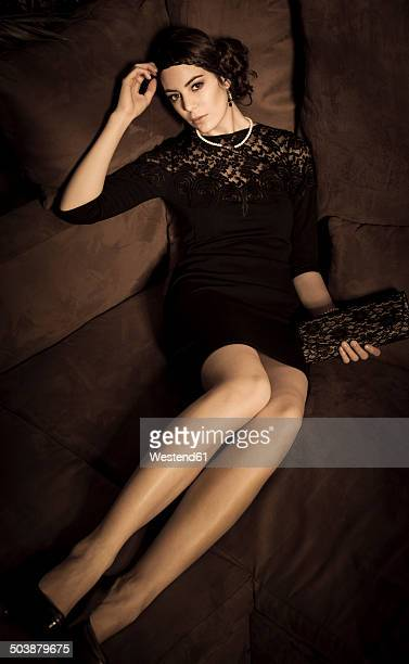 Portrait of young woman with little black dress and handbag lying on couch