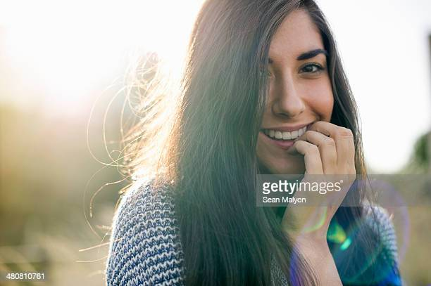 portrait of young woman with long brown hair, smiling - verlegen stockfoto's en -beelden