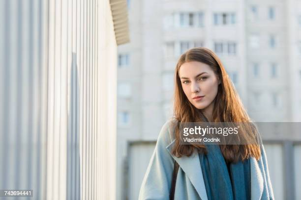 Portrait of young woman with long brown hair standing by wall in city