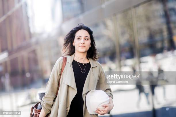 portrait of young woman with long brown hair wearing beige coat, holding hard hat, looking at camera. - sigrid gombert stock pictures, royalty-free photos & images
