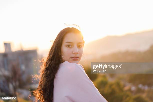 Portrait of young woman with long curly hair at evening twilight