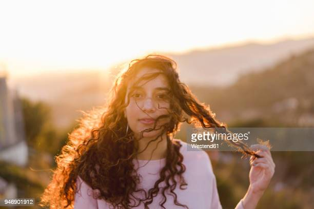 Portrait of young woman with long curly hair at sunset