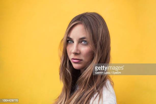 Portrait Of Young Woman With Long Hair Against Yellow Background