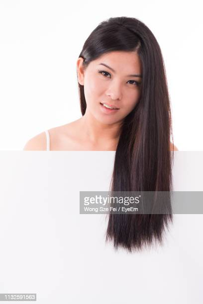 portrait of young woman with long hair holding blank placard while standing against white background - ストレートヘア ストックフォトと画像