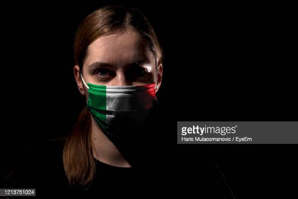portrait of young woman with mask on black background corona covid-19 - coronavirus italia foto e immagini stock