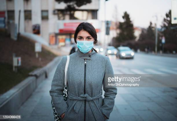 portrait of young woman with mask on the street. - protection stock pictures, royalty-free photos & images