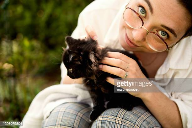 "portrait of young woman with newly adopted kitten. - ""martine doucet"" or martinedoucet stock pictures, royalty-free photos & images"