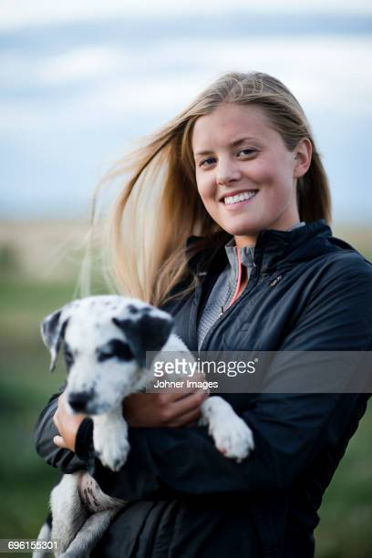 Portrait of young woman with puppy in field