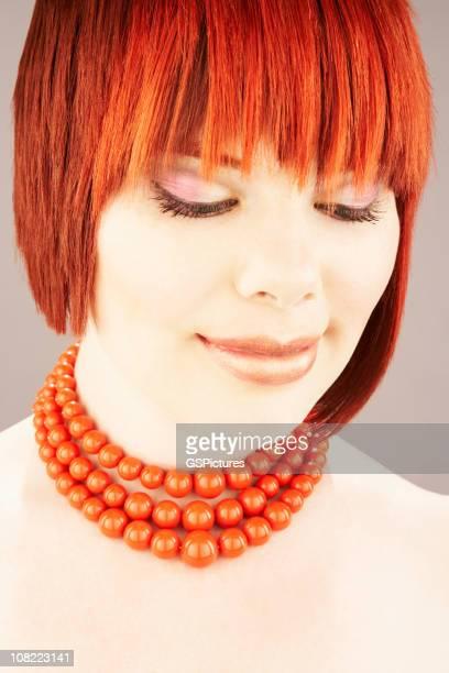 Retrato de mujer joven con pelo rojo mirando hacia abajo