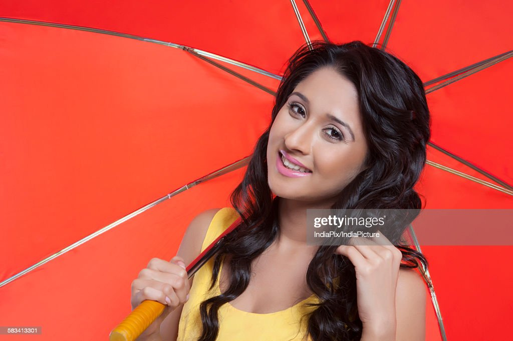 Portrait of young woman with red umbrella : Stock Photo