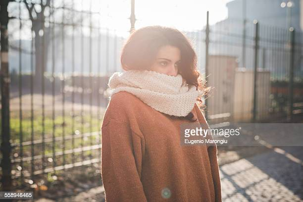 Portrait of young woman with scarf covering mouth in park