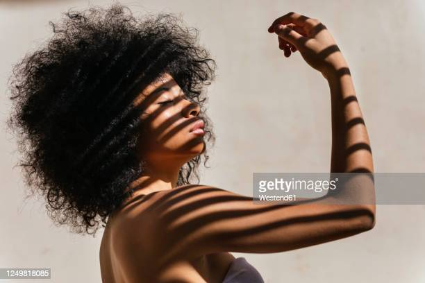 portrait of young woman with shadow on her body - curly stock pictures, royalty-free photos & images
