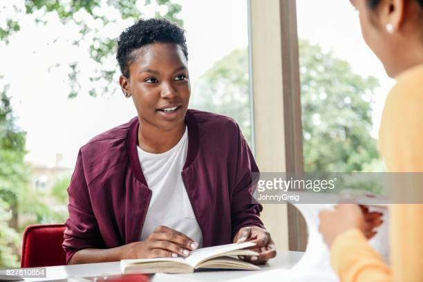 portrait of young woman with short black hair reading book, looking towards friend - bomber jacket stock pictures, royalty-free photos & images