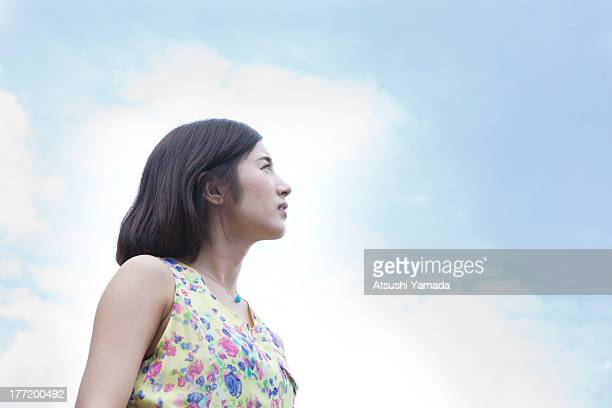 Portrait of young woman with sky background