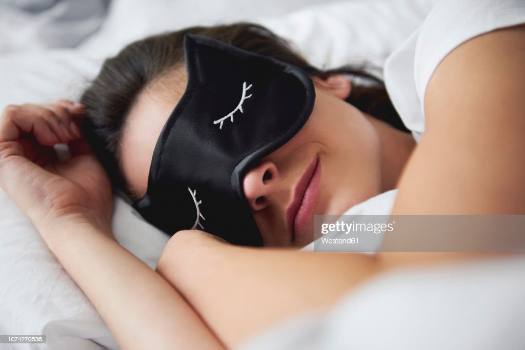 Portrait of young woman with sleep mask in bed : Stockfoto