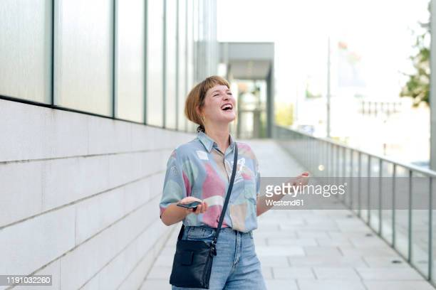 portrait of young woman with smartphone freaking out - crossbody bag stock pictures, royalty-free photos & images
