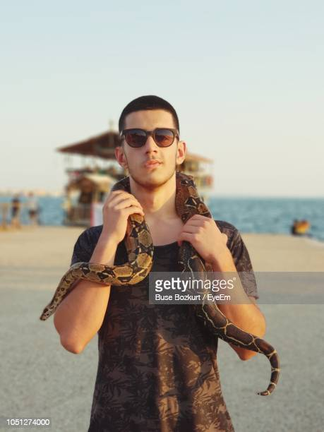 Portrait Of Young Woman With Snake Wearing Sunglasses Standing At Beach