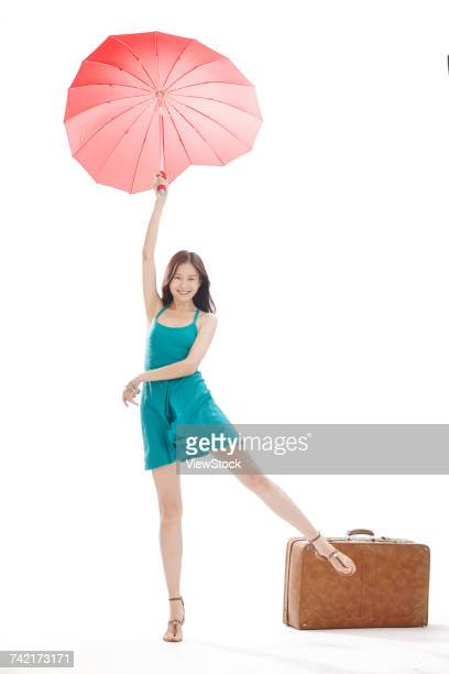 Portrait of young woman with suitcase and sun umbrella