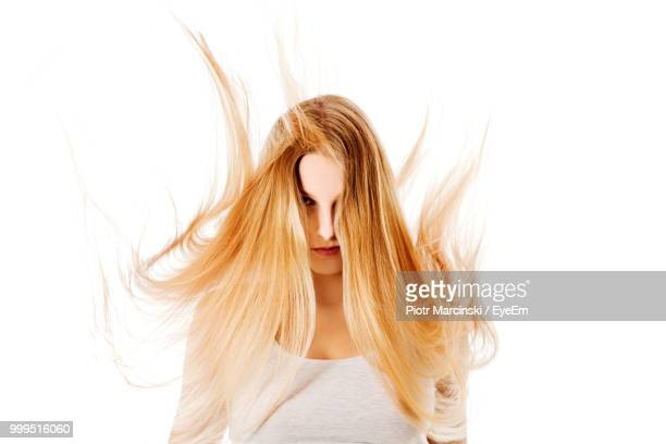 portrait of young woman with tousled hair against white background - warrig haar stockfoto's en -beelden