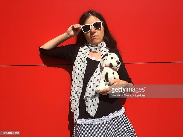 portrait of young woman with toy dog against red wall - toy animal stock photos and pictures